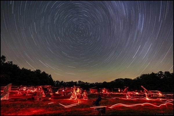 رد ستارهای (دور قطبی) همراه با ستاره قطبی در مرکز و رصدگرانی که با چراغ قوه قرمز در منطقه فعالیت میکنند.